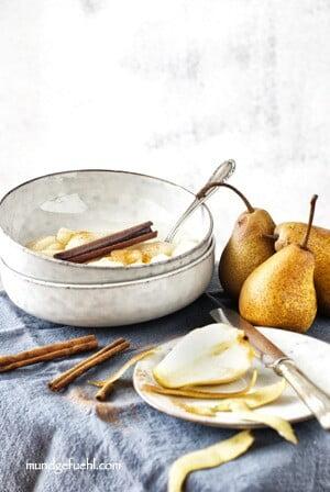 aufgeschnittene und geschälte Birne steht vor 2 Schüsseln mit Birnenkompott