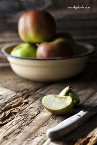 Ein aufgeschnittener Apfel liegt vor einer Schüssel mit Äpfeln