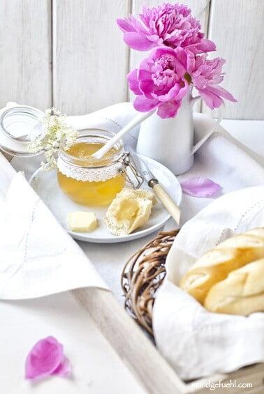 Tablett mit Marmelade, Brötchen und Blumen