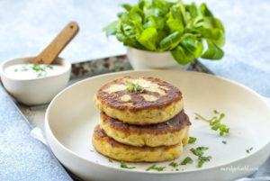 Topfen-Kartoffellaibchen liegen auf einem Teller. Dahinter steht eine Dipschale und eine Schale mit Vogerlsalat