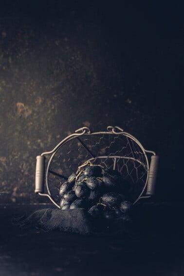 Eine Traubenrispe liegt in einem umgefallenen Korb
