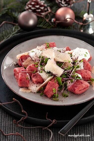 Ein Teller mit Rote Bete Gnocchi und Dip mit einem weihnachtlichen Gedeck