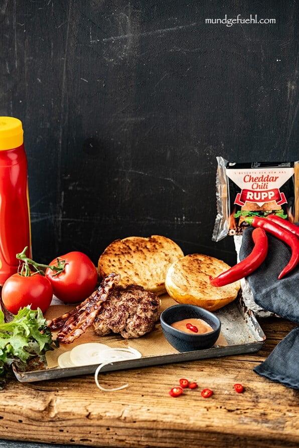 Zutaten für einen Rindfleisch-Burger stehen am Tisch