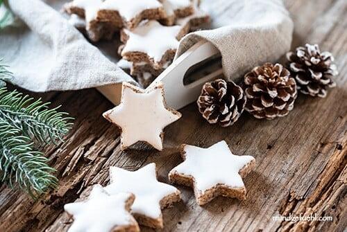 Einige Zimtsterne liegen mit Weihnachtsdekoration am Tisch