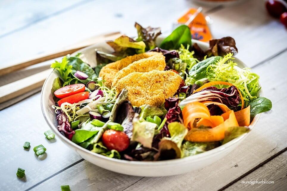 Bunter Salat wurde mit Kartoffel-Kürbis-Ecken auf einem Teller angerichtet