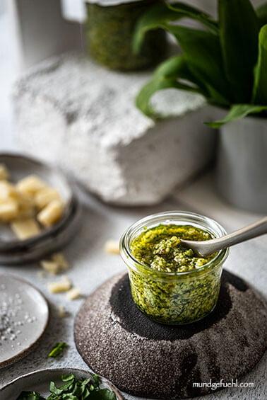 Pesto mit Bärlauch steht mit einzelnen Zutaten am Tisch