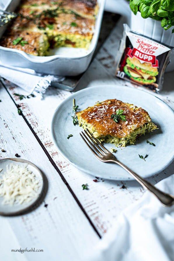 Ein Stück Zucchini Auflauf mit Ricotta liegt auf einem Teller