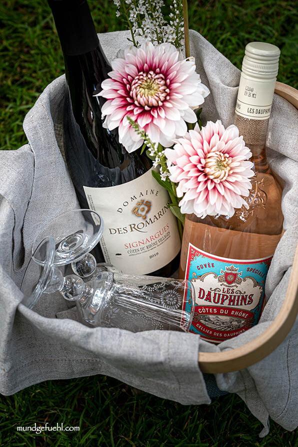2 Weinflaschen und 2 Weingläser in einem Korb
